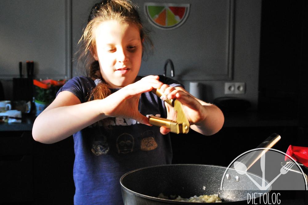 Milena przeciska czosnek praską do czosnku